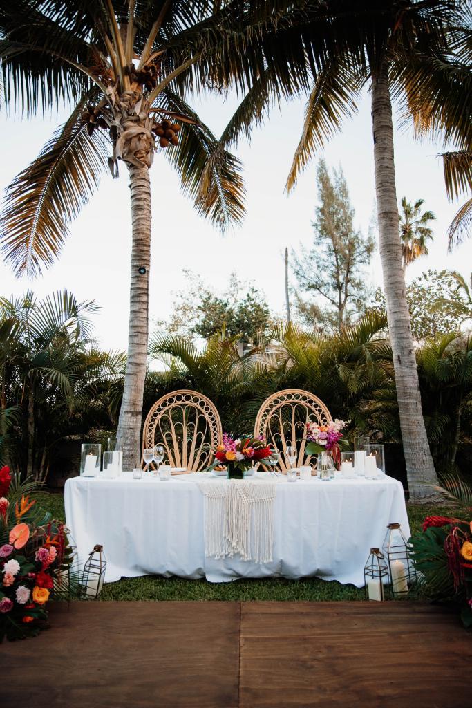 tropical bohemian destination wedding sweetheart table peacock chairs